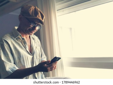 Man with cap and glasses consults his mobile phone