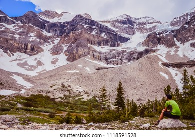 Man with a cap and green t-shirt is sitting and watching high mountains with trees and moraines on the sides. Stanley glacier trail in Kootenay national park in British columbia, Canada.