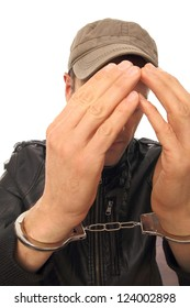 Man with cap and Handcuffs in front of his face