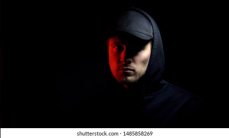 Man in cap and hoodie looking at camera, red light, police raid, catching thief