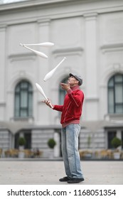 A man in a cap juggles with clubs on the street of a European city