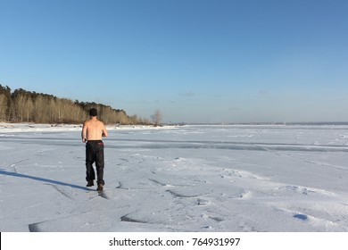 Man in a cap with a naked torso running across the ice of a frozen river, Ob Reservoir, Russia