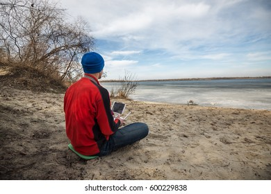 Man in a cap sits on the beach with a remote controller in his hands and attentively monitors the flight of the drone over the surface of the water. Spring day on the coast. Back view.