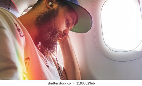 man in a cap is sitting and listens to an audiobook in headphones by the window in the plane