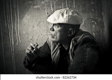 The man in a cap smokes a cigaret against a dirty wall