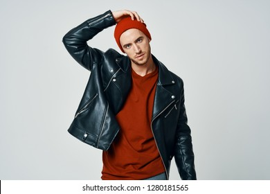 A man in a cap and a sweater in a leather jacket