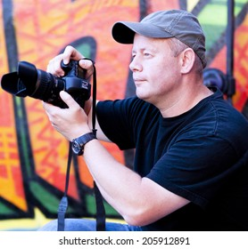 Man in cap taking photos with graffiti background