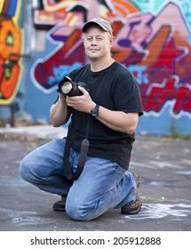 Man in cap taking photos near graffiti wall