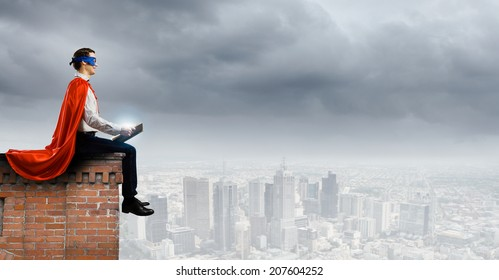 man in cape and mask sitting on top of building and reading book
