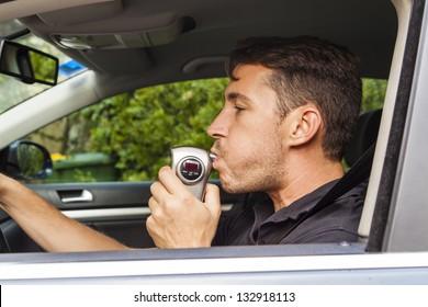 Man in car blowing into breathalyzer