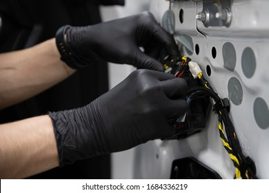 Man car factory or service worker assembles car electrical equipment