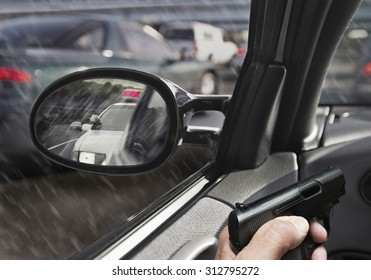 man in car with gun police car in sideview mirror