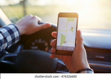 Man in the car and holding black mobile phone with map gps navigation, toned at sunset.