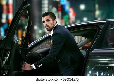 man and car lights lit, night city