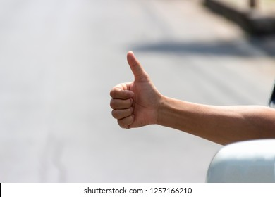 A man in car is showing thumbs up sign during travel