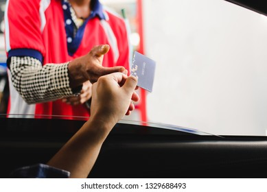Man in a car using a debit card, young man holding payment card used to pay for gasoline, diesel, and other fuels at gas stations, Driver with fleet cards for refueling car,copy space.