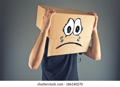 Man with cardboard box on his head and sad crying emoticon face expression. Concept of sadness and depression.