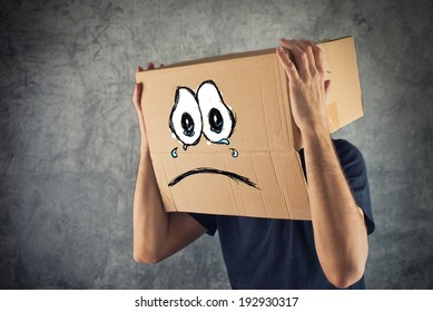 Man with cardboard box on his head and sad crying face expression. Concept of sadness and depression.