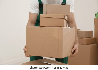 Man with cardboard boxes in room, closeup. Moving service