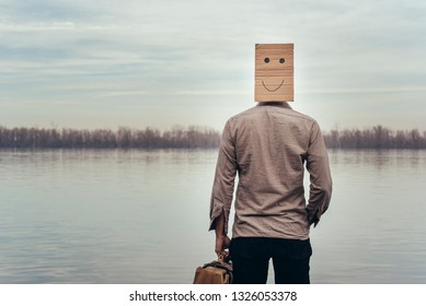 Man with a cardboard face and a suitcase on the bank of the river