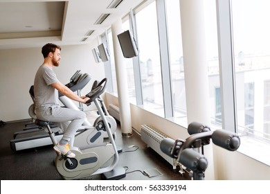 Man cardio training on a bicycle in a gym