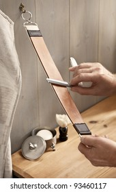 A man carefully stropping his straight razor