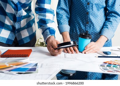 Man carefully studying technical drawing with magnifying glass. Designers working with color swatches and construction blueprint at workplace. Thorough analysis and inspection of design project.