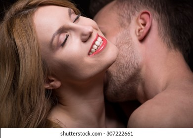 Man caressing and kissing woman's neck during foreplay