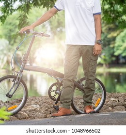 Man with cargo pants riding a bicycle in the garden