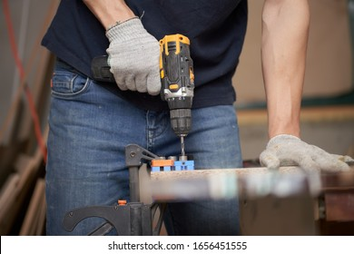 Man carpenter with drill and board in workshop