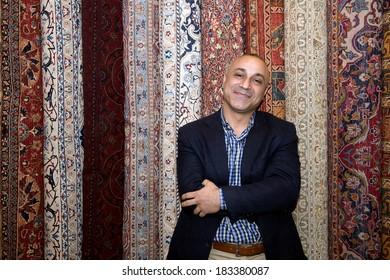 Man in carpet shops posing with his carpets