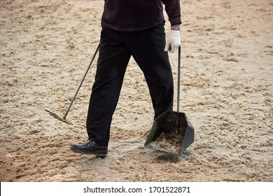 A man carries away horse manure removed from a racetrack