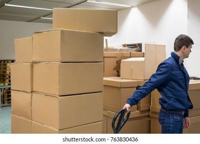 Man carries boxes by pallet tracker on production warehouse. Closed up.