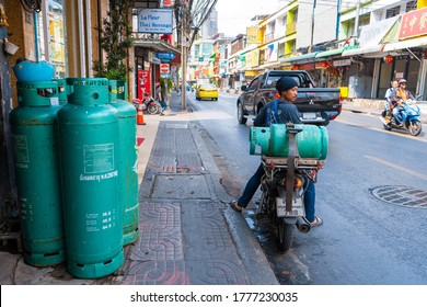 A man carries a gas cylinder on a motobike. Delivery of gas cylinders in Thailand. Bangkok / Tailand - 02.04.2020
