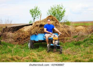 The man carries hay on a cart.