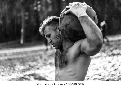 man carries a heavy stone - Obstacle Race, Sports Competition