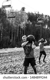 man carries a heavy stone - Obstacle Race, Sports Competition Belarus, May 2019
