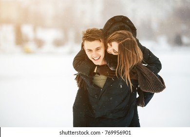 man carries his girlfriend on the back in the park, in winter holidays