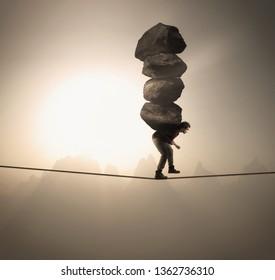 El hombre carga una pila de grandes rocas mientras se balancea en una cuerda a gran altura.