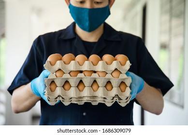 Ein Mann trägt 3-Lagen-Eier-Tray, um zu Hause sicher zu bleiben und Sanitärhandschuh während des Corona-Virus COVID-19 Ausbreitung - Menschen, die Lebensmittel in COVID-19 virale Spread-Periode Konzept.