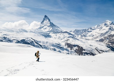 A man carry the snow ball with the background of Matterhorn.