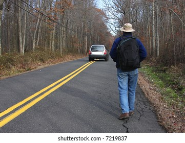 Man carrying a backpack hiking down a country road in fall