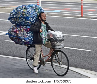 Man  carrying bags of aluminum cans on a bike in Tokyo  for recycling. Taken on April 25, 2019