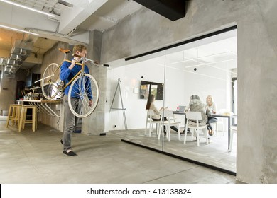 Man carrying a bicycle in the office