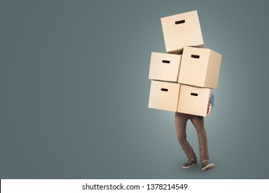 A man is carrying a big stack of cardboard boxes in his arms