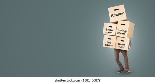 Man carrying a big stack of moving boxes labeled with different rooms