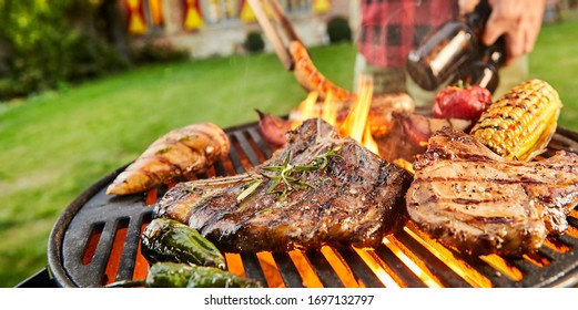 Man carrying bottles ob beer barbecuing outdoors in a close up view on assorted meat grilling over the flaming hot coals