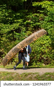 Man carrying a camouflaged canoe