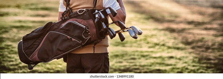 Man carrying golf bag while standing on field, Rear view