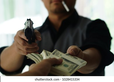 Man carrying a gun to rob the money.  The bad man hold gun to rob in the bank. Thief or robber in black Shirt  with gun threatens man or woman for steal money on street, dangerous criminal in the city